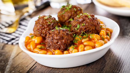 baked beans: hearty meatballs with parsley and baked beans Stock Photo