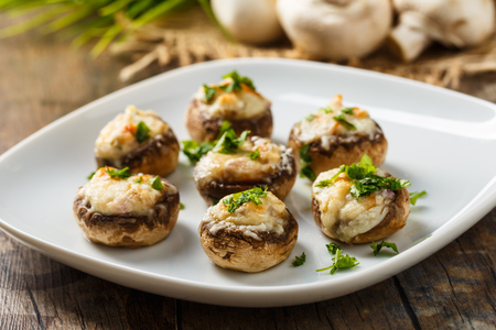 Stuffed mushrooms with parmesan crust and fresh herbs. Stock Photo