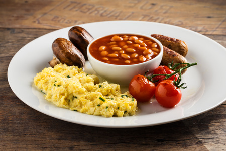Breakfast with sausages, scrambled eggs, baked beans, mushrooms and tomatoes.