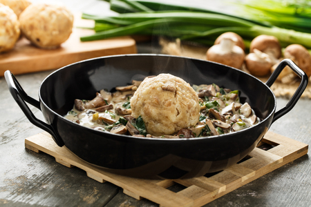 Homemade bavarian bread dumpling with creamed mushrooms and herbs. Stock Photo