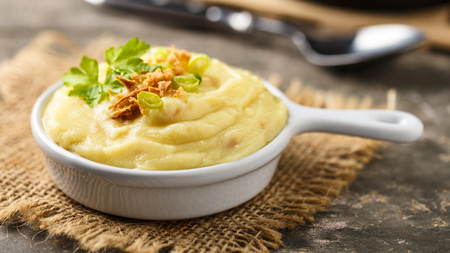 Mashed potatoes with roasted onions served in a small bowl.