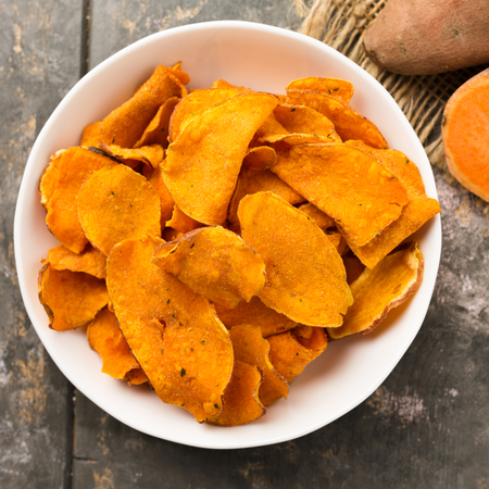 Hearty sweet potato crisps served in a bowl. Stock Photo