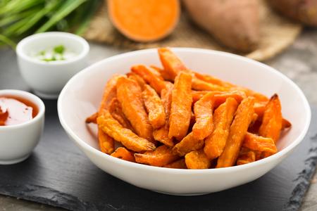 Herzhafte Süßkartoffel-Pommes in einer Schüssel serviert. Standard-Bild - 75427019
