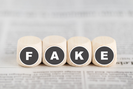 """Fake news - the words """"fake"""" on cubes on a newspaper Standard-Bild - 99482095"""