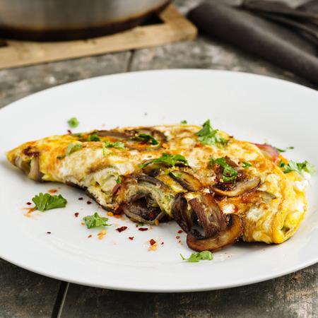 Fresh homemade omelette with mushrooms, feta cheese and herbs. Standard-Bild - 100458054