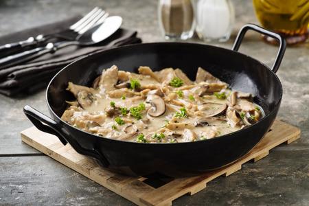 Vegan soy meat stripes and mushrooms in creamy sauce Standard-Bild - 100760043