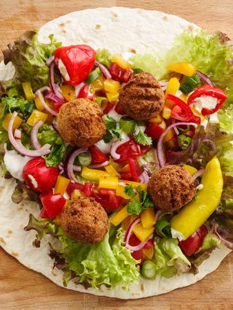 fresh falafel wrap with veggies, ready to roll Standard-Bild - 111759615