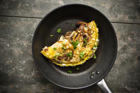 Fresh homemade omelette with mushrooms, feta cheese and herbs. Standard-Bild - 111759616