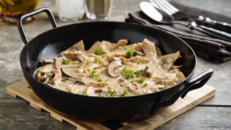 Vegan soy meat stripes and mushrooms in creamy sauce Standard-Bild - 111759619