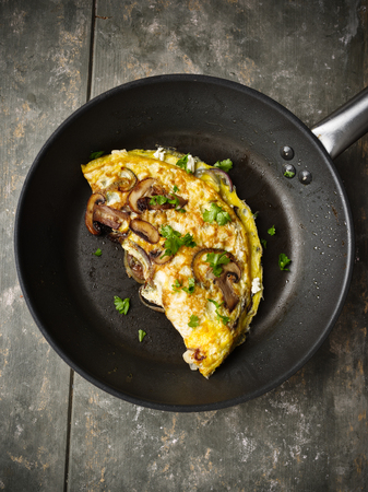 Fresh homemade omelette with mushrooms, feta cheese and herbs. Standard-Bild - 104635267