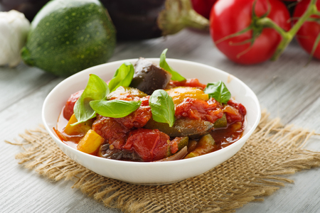 Ratatouille - french vegetable stew with tomotoes, aubergines, courgettes and peppers. Standard-Bild - 104882496