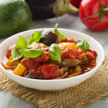 Ratatouille - french vegetable stew with tomotoes, aubergines, courgettes and peppers. Standard-Bild - 111759629