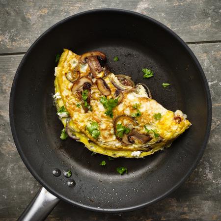 Fresh homemade omelette with mushrooms, feta cheese and herbs. Standard-Bild - 111759632
