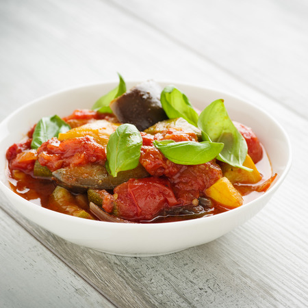 Ratatouille - french vegetable stew with tomotoes, aubergines, courgettes and peppers. Standard-Bild - 105298951