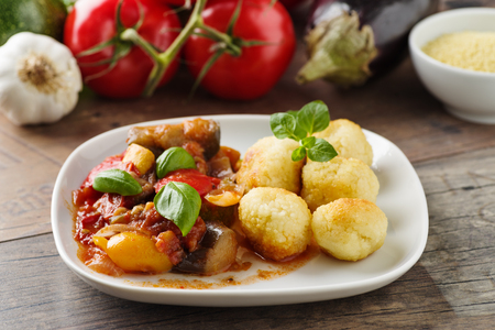 Ratatouille - french vegetable stew with tomotoes, aubergines, courgettes and peppers. Served with couscous balls Standard-Bild - 111759696