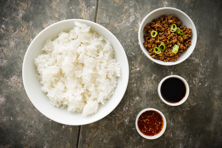 Korean Soy Beef Bowl - dish with rice, soy meat and chili sauce Standard-Bild - 111759697