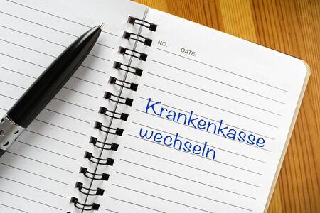 "Notepad with german phrase ""Krankenkasse wechseln"". Translation: switch health insurance"