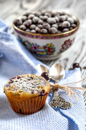 blackcurrant: Muffin, two silver spoons, a Cup with blackcurrant, blue napkin on a rustic background