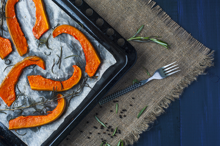 baking tray: Slices of baked pumpkin on baking tray with fork, leaves of rosemary, black pepper on brown burlap napkin