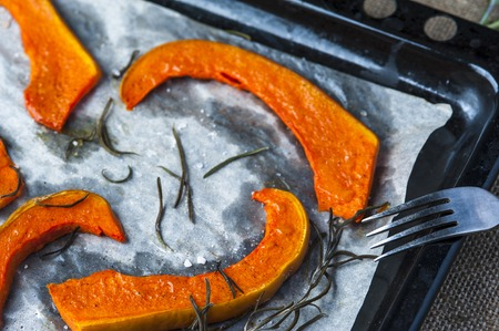 cooking oil: Slices of baked pumpkin on baking tray with fork, leaves of rosemary, black pepper on brown burlap napkin. Stock Photo