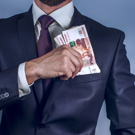 Bearded man removes Russian rubles in his suit pocket on a grey background.