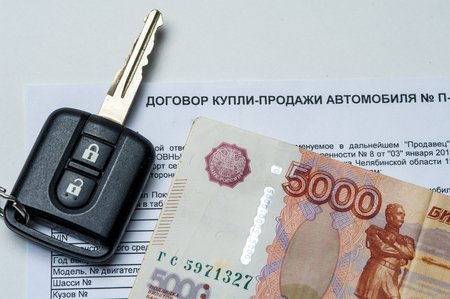 purchased: The contract of purchase of the car, Russian banknotes and car key on white background.