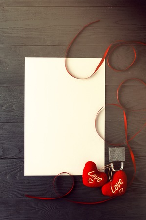 bonded: Two hearts bonded in lock, white sheet and red ribbon on dark wooden background. Stock Photo