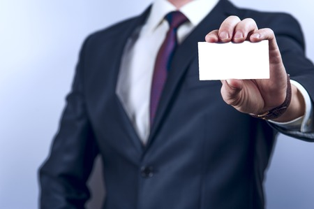 Man in dark suit holds business card on grey background. Focus on card and fingers. Horizontal view. Stock Photo