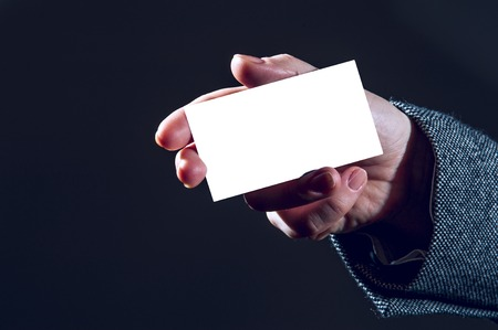 notecard: Womans hand holding white business card on black background. Focus on card and fingers. Horizontal view.