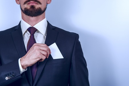 notecard: Bearded man in dark suit removes business card to his suit pocket. Horizontal view. Stock Photo