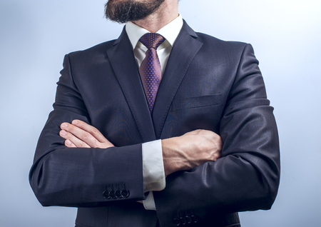 human wrist: Bearded man in dark suit crossing his arms on chest. Horizontal view.