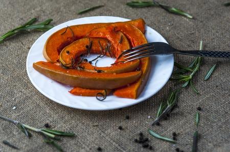 horisontal: Slices of baked pumpkin on white plate with fork, leaves of rosemary, black pepper on brown burlap napkin. Horisontal view.