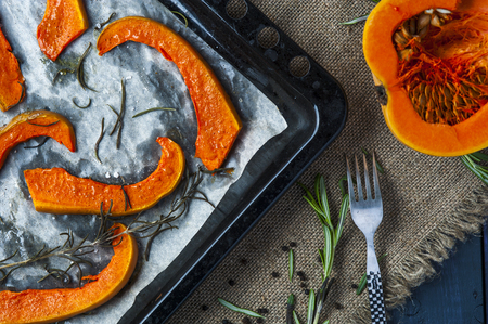 Slices of baked pumpkin on baking tray with fork, leaves of rosemary, black pepper anh a half of pumpkin on brown burlap napkin. Square frame. Dark blue background. Focus on pumpkin slices. Standard-Bild