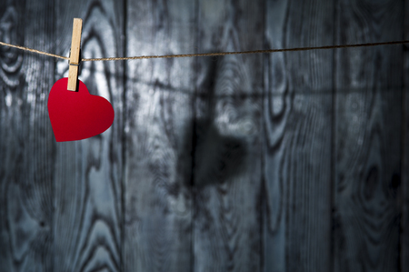 Red heart with clothespin on linen rope. Shadow heart on the wooden background. Horizontal view. Valentines theme.