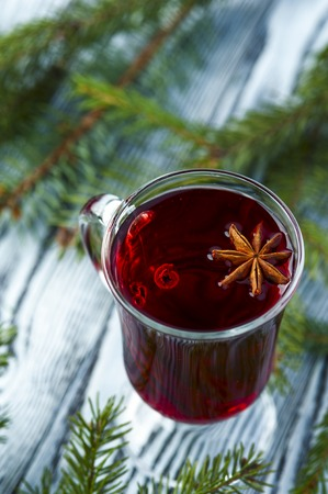 brunches: Homemade mulled wine with star anise and cinnamon sticks on the rustic background with spruce brunches. Winter theme. Focus on star anise. Vertical view. Stock Photo
