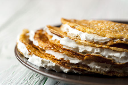 pancake week: Homemade pancakes on brown plate with Whipped cream on wooden rustic background. Russian holiday pancake week. Focus on pancakes. Horizontal view.