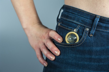 safe sex: Woman with condom in jeans pocket. The concept of safe sex. Focus on condom. Horizontal view.