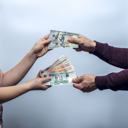 fall protection: The man and the woman exchange US dollars and Russian rubles on grey background. The fall of the ruble. Conception of safe storage and protection of cash. Financial theme. Stock Photo