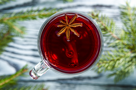 brunches: Homemade mulled wine with star anise and cinnamon sticks on the rustic background with spruce brunches. Winter theme. Focus on star anise. Top view.
