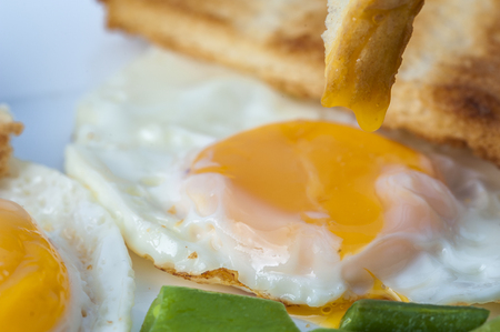 beans on toast: Close up of fried eggs, green beans with piece of toast on white plate. English breakfast. Horizontal view.