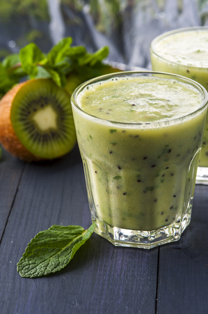 nonalcoholic: Two glasses of homemade smoothie with kiwi, banana and mint leaves . Conception of healthy food.  Nonalcoholic drinks.