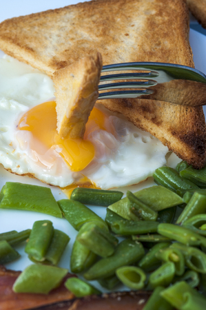 beans on toast: Fried egg, bacon, green beans and fork with piece of toast. English breakfast. Vertical view. Focus on yolk. Stock Photo