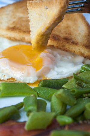 beans on toast: Fried eggs, bacon, green beans and fork with piece of toast on white plate. English breakfast. Vertical view. Focus on egg. Stock Photo