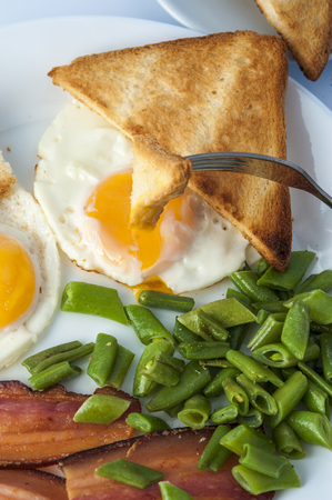 beans on toast: Fried eggs, bacon, green beans and fork with piece of toast on white plate. English breakfast. Vertical view.