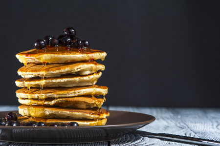 pancake week: Stack of homemade pancakes with berries and honey on brown plate on rustic background. Russian holiday pancake week. Focus on pancakes. Horizontal view. Stock Photo