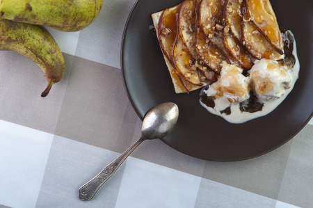pan tropical: Tarte with puff pastry, pears, walnuts and ice cream on brown plate and silver spoon