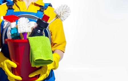 mucama: La mujer sostiene un cubo de suministros para la limpieza. Aislado en el fondo blanco.