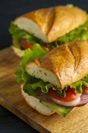 Baguette with ham, vegetable slices and lettuce on wooden table. Fast food