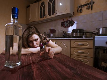 alcoholismo: mujer depresiva borracho sostiene el vidrio vac�o y se ve en la botella con alcohol. alcoholismo en las mujeres.
