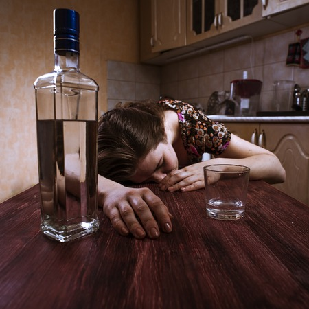 drunk girl: Lonely Drunk woman sleeping on the table on kitchen. Female alcoholism. Selective focus.